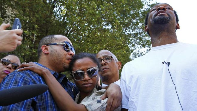 """Stephen Mattingly (left) consoles his step sister, Kristen Unsled, while Tracy Anderson speaks with the media during a news conference outside of University of Louisville hospital, June 10, 2015. Mattingly's brother and local rap artist, Donald """"Wreck D. Mic"""" Mattingly Jr., died in the hospital Tuesday after being gunned down Monday, alongside Henry Anderson Jr, outside of a local club. Anderson is still fighting for his life."""