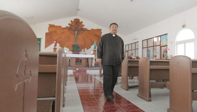Father Mike Crisostomo, pastor of the Immaculate Heart of Mary Church in Toto, walks the center aisle of the church in July 2014.