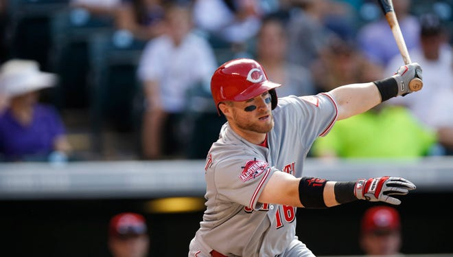 Cincinnati Reds catcher Tucker Barnhart (16) bats against the Colorado Rockies in the seventh inning of a baseball game Sunday, July 26, 2015, in Denver. Colorado won 17-7. (AP Photo/David Zalubowski)