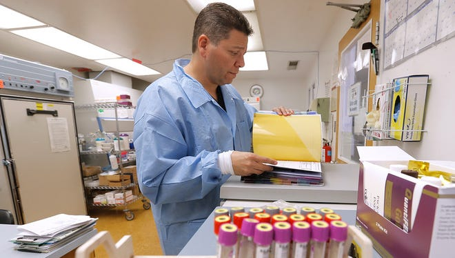 City of El Paso Department of Public Health Senior Microbiologist Cesar Moreno works in his lab the Tillman Health Center in Downtown El Paso, where tuberculosis tests were being processed.