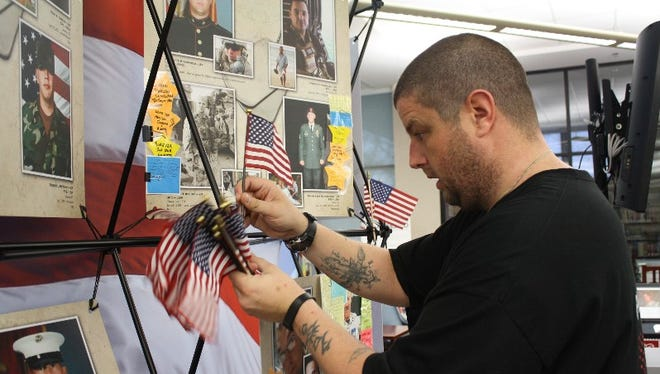 Marine veteran Trey Obert, with Indianapolis-based Crossroads Veteran Services, an Easter Seals program, sets up the Remembering Our Fallen display in the Jeffersonville Township Public Library on Friday, January 22, 2016.