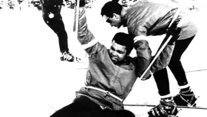 Boxer Muhammad Ali is helped up by instructor Bob Gratton after a fall during a 1970 lesson at Mount Snow in West Dover.