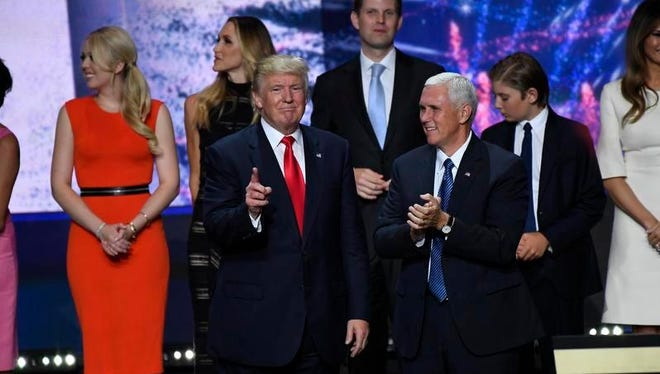 Donald Trump , Mike Pence and their families acknowledge the crowd after Trump delivered his speech during the 2016 Republican National Convention at Quicken Loans Arena.