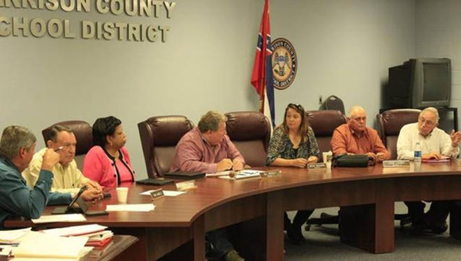 Harrison County School Board members work Monday during their regular meeting. They met with a woman in closed session during that meeting who said her son had been forced to stand during the Pledge of Allegiance and threatened with punishment when he refused.