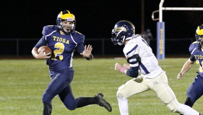 Connor Hutchinson carries the ball for Tioga as Elmira Notre Dame's Gary Raupers comes up to try to make the tackle Friday night in a Section 4 Class D quarterfinal at Tioga.