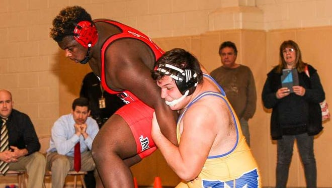 Manville High School's Michael Tyle (gold singlet) wrestles Bound Brook's J.J. Sistrunk in the heavyweight final of the Bear Invitational