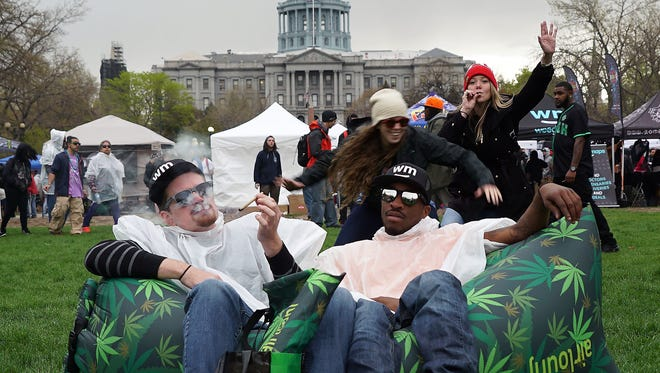 Two men share a joint April 20, 2017, in front of the Colorado state capitol in Denver during the annual 4/20 rally.
