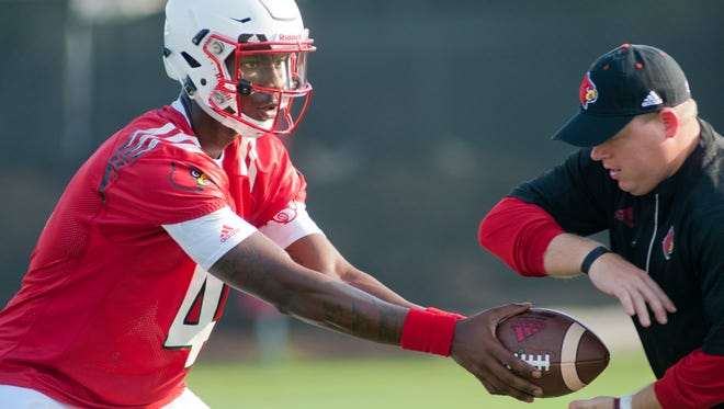 Nate Petrino, son of University of Louisville Cardinals' football head coach Bobby Petrino, takes a handoff from freshman quarterback Jawon Pass during the team's first practice of the season. Nate is an assistant coach on his father's team.03 August 2016502-262-2258