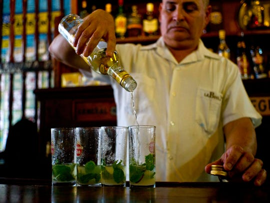 "In this Friday, April 28, 2017 photo, a bartender pours Cuban Havana Club rum to prepare ""mojitos"" at the Bodeguita Del Medio bar in Havana, Cuba. The agency that controls Pennsylvania's state-owned wine and liquor stores is working to lift the embargo on Cuban rum. (AP Photo/Ramon Espinosa)"