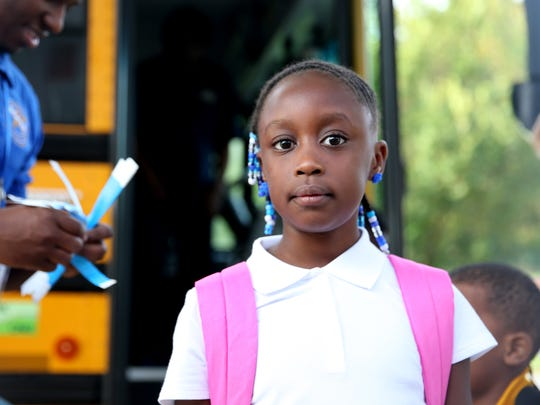 Jayda Riley, 8, gets off the bus at Apalachee Elementary School Monday, the first day back for Leon County students.
