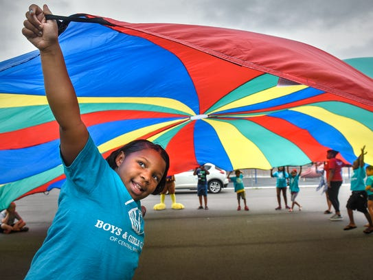 Children play with a large brightly-colored parachute