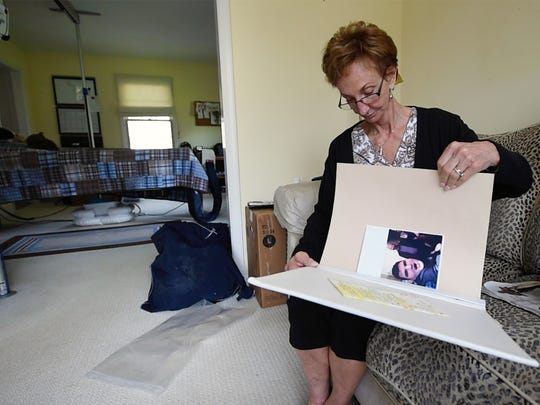 Linda Yurchak, grandmother, looks through a scrapbook of about Carson McCord's life next to his bedroom at his York Township home.