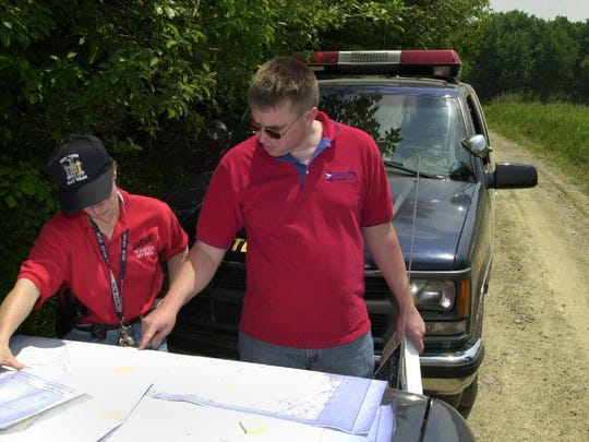 At the end of Evelien Hill Road in the Town of Candor, BCI Investigators Lori Hochdanner, left, and Steve Andersen check their maps before continuing their June 2002 search of Michele Harris, who disappeared Sept. 11, 2001.