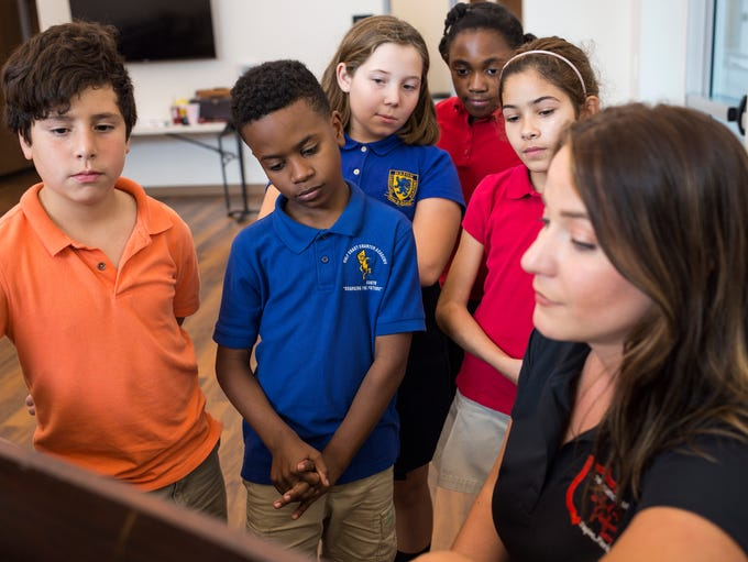 Students gather around the piano as School of Performing