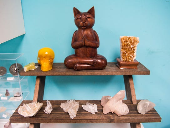 A cat figurine and crystals are displayed for sale