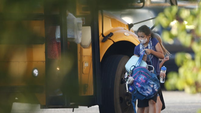 Oconee County Middle School students get off the bus for the first day of classes in Watkinsville on Aug. 5.