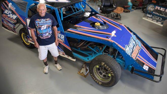 Bud Frazier stands in his son's garage beside the car in which he competes. Frazier started racing in the 1960s when safety precautions were less prevalent in racing and admits he has seen a lot of changes in his almost half-century career.