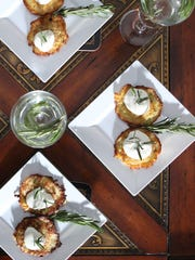 Vodka garnished with a sprig of rosemary served with potato latkes garnished with sour cream and rosemary.