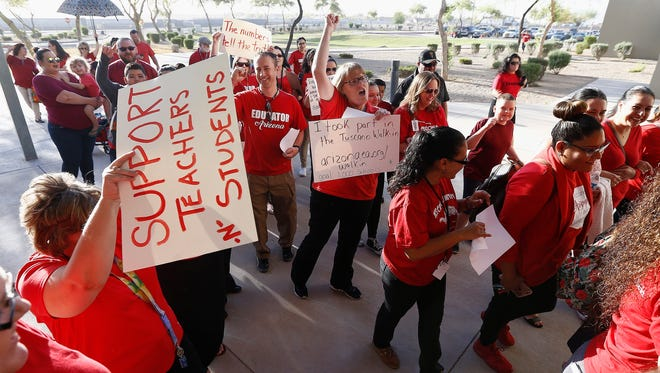 """Teachers at Tuscano Elementary School stage a """"walk-in"""" for higher pay and school funding as they arrive at the front entrance of the school on April 11, 2018, in Phoenix. Teachers gathered outside Arizona schools to show solidarity in their demand for higher salaries staging """"walk-ins"""" at approximately 1,000 schools that are part of a statewide campaign for a 20 percent raise and more than $1 billion in new education funding."""