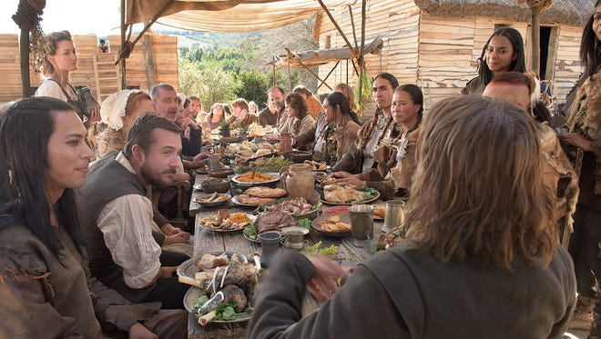 """Pilgrims and their Wampanoag guests share the first Thanksgiving meal in a scene from National Geographic Channels two-night movie event """"Saints & Strangers."""""""