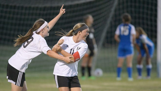 Lexington's Chandler Holmes (19) and Molly Lewis (11) celebrate the Lady Tigers' 2-1 extra time victory over the Chester County Lady Eagles at Nathan Cagle Field in Lexington, Tenn., on Tuesday, Sept. 22, 2015.