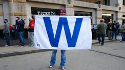 A Cubs fan holds up the 'W' flag before Game 1 in Cleveland.