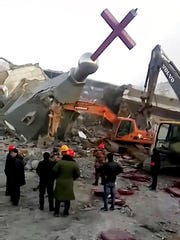 In this image taken from video shot Tuesday, Jan. 9, 2018, by China Aid and provided to the Associated Press, people in hard hats stand amid the remains of the Golden Lampstand Church in Linfen in northern China's Shanxi province. Witnesses and overseas activists say paramilitary troops known as the People's Armed Police used excavators and dynamite on Tuesday to destroy the Golden Lampstand Church, a Christian mega-church that clashed with the government.