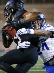 University of Memphis defensive back Tito Windham (right) brings down University of Tulsa receiver Justin Hobbs (left) during first quarter action in Tulsa, Okla., Friday, November 3, 2017.