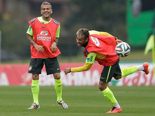 Brazil's Neymar, right, and Dani Alves, practice during a training session of the Brazilian national soccer team at the Granja Comary training center in Teresopolis, Brazil, Saturday, June 21, 2014. Brazil plays in group A of the 2014 soccer World Cup. (AP Photo/Andre Penner)