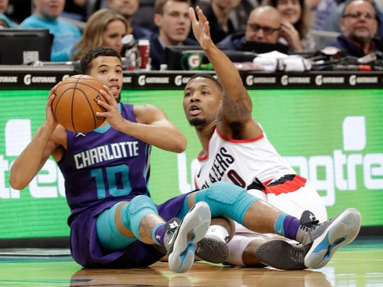 Charlotte Hornets' Michael Carter-Williams (10) looks to pass as Portland Trail Blazers' Damian Lillard (0) defends during the first half of an NBA basketball game in Charlotte, N.C., Saturday, Dec. 16, 2017. (AP Photo/Chuck Burton)