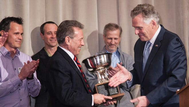 Al Schornberg, left, owner of Keswick Vineyards, accepts the Governor's Cup award from Virginia Gov. Terry McAuliffe.