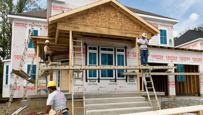 Construction workers build a new home in Bristow, Virginia.