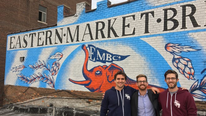 From left, Eastern Market Brewing Co. co-owners Paul Hoskin, Dayne Bartscht and Devin Drowley plan to open the brewery in spring 2017 on Riopelle in Eastern Market. They're pictured here Oct. 12, 2016 next to the brewery's mural.