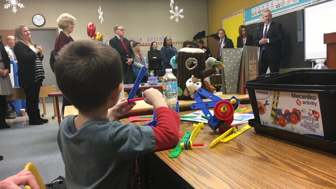 Future Grissom preschool student Brice Wooten tries out some toys while community members talk during the preview event Tuesday. The preschool class starts in January.
