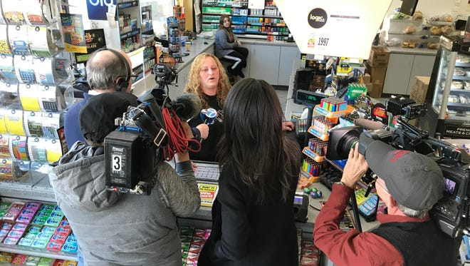 An attendant speaks to reporters after the New Jersey Lottery announced that Friday's winning Mega Millions ticket, now worth $533 million, was sold at the Lukoil station on Route 23 south in Riverdale.