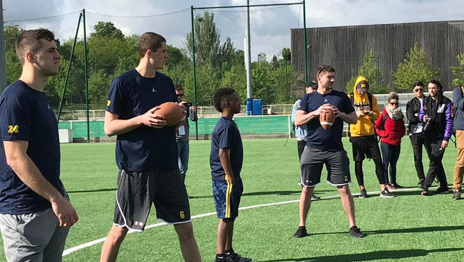 Michigan quarterbacks Brandon Peters (far right) and Shea Patterson (far left) play catch April 28, 2018 in Paris.