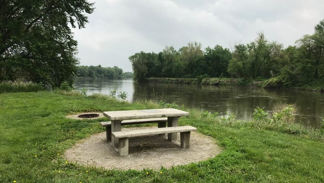 A picnic table and fire pit are shown at River Junction Park along the Iowa River in Lone Tree on May 21, 2018.