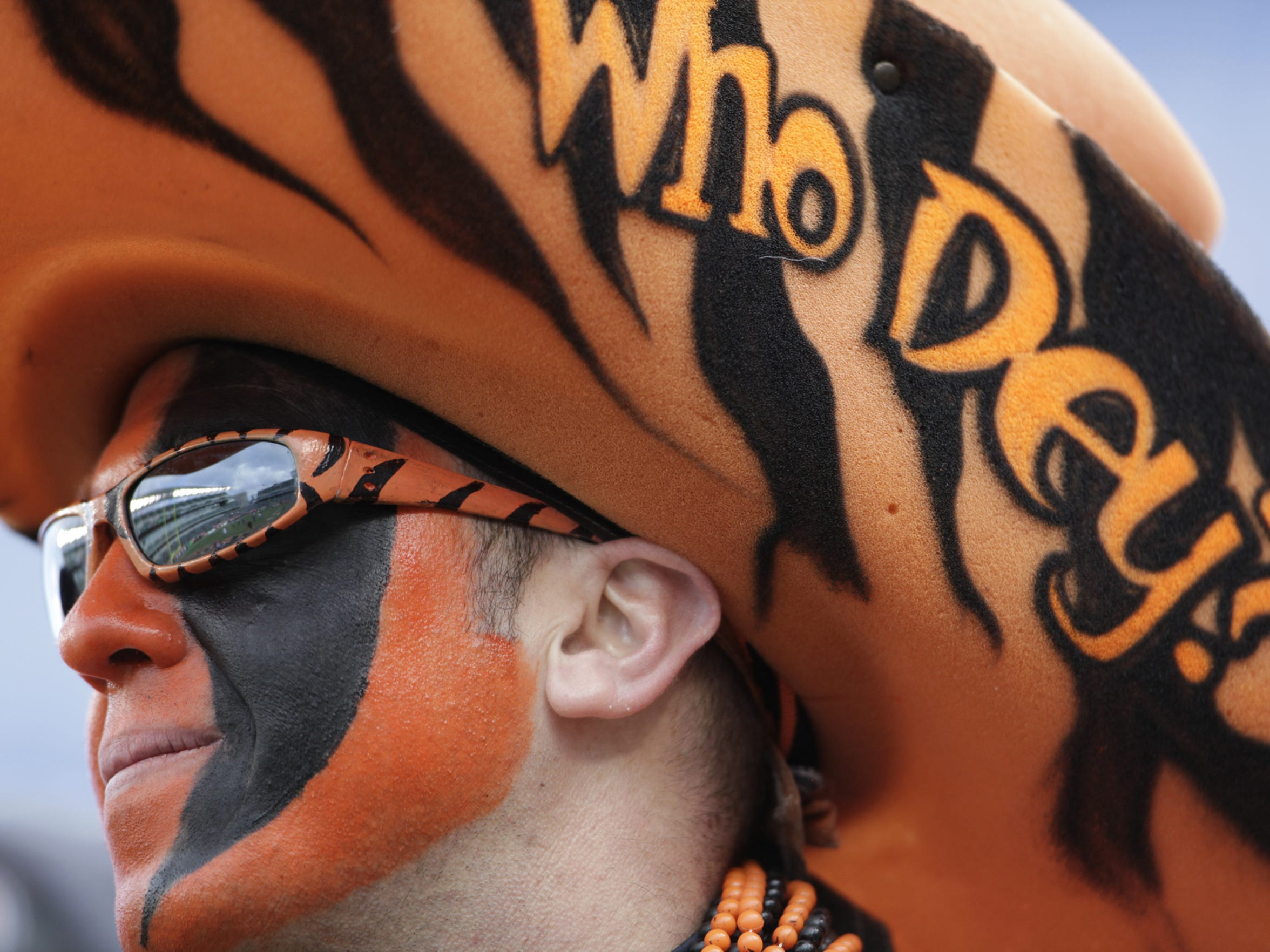 Shaun Moore of Columbus accessorized his giant Who Dey hat with orange and black striped glasses and face paint in 2012.