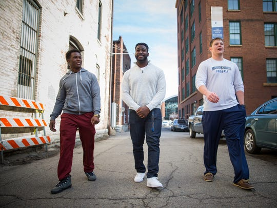 From left, Maurice Woodard, running back on the Marian University Knights' football team, Darrion McAlister, center for the offensive line, and Ryan Borders, fellow lineman and right guard alongside McAlister, walk together in downtown Indianapolis. McAlister wants to play his final season open and honest about who he is. McAlister knew in eighth grade that he was gay but is just coming out to his friends and family.