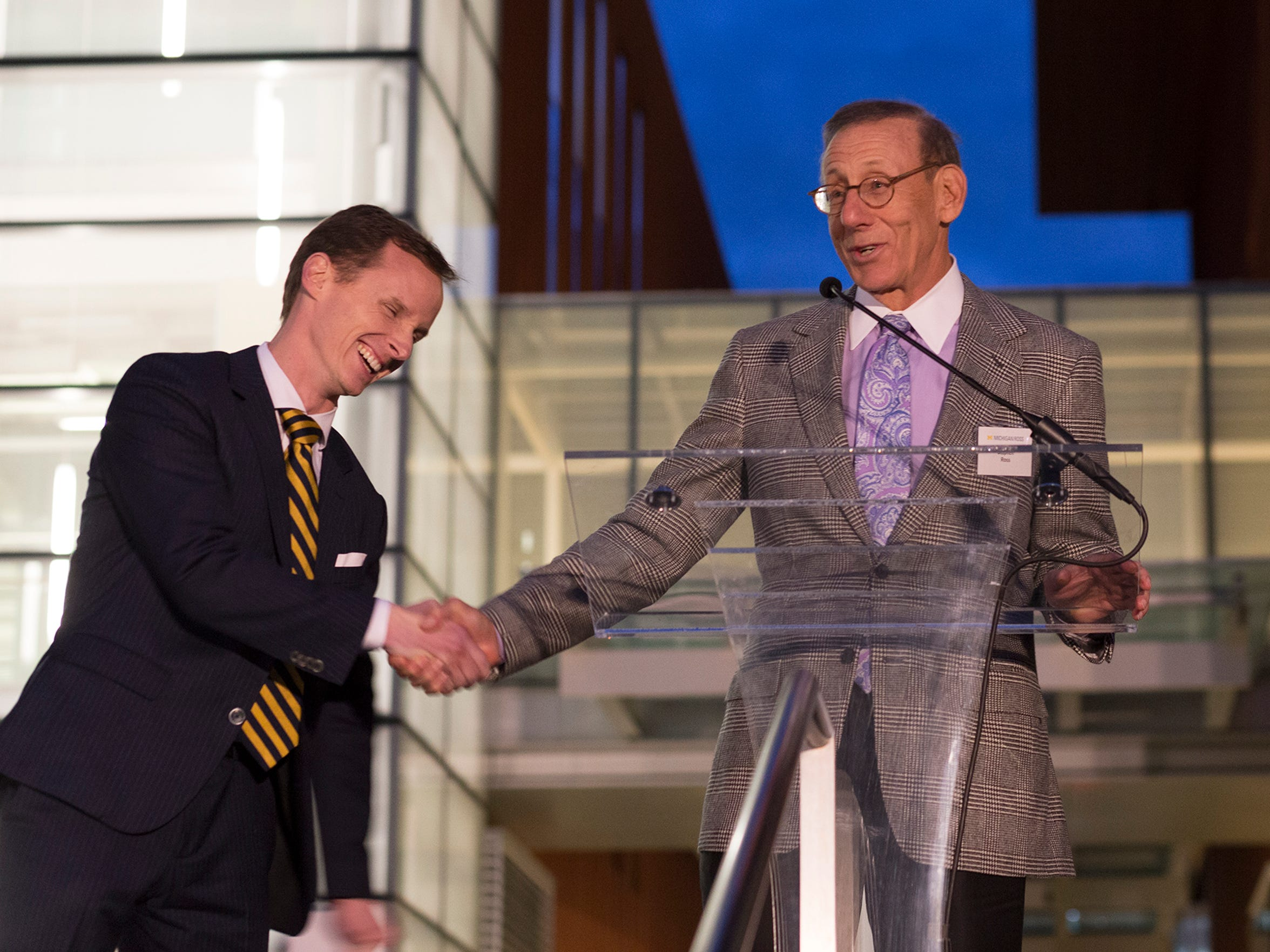 Stephen Ross, right, shakes the hand of Scott DeRue, the Edward J. Frey Dean of the Ross School of Business, during the ribbon cutting ceremony celebrating the Jeff T. Blau Hall on Oct. 21, 2016 at the University of Michigan in Ann Arbor.