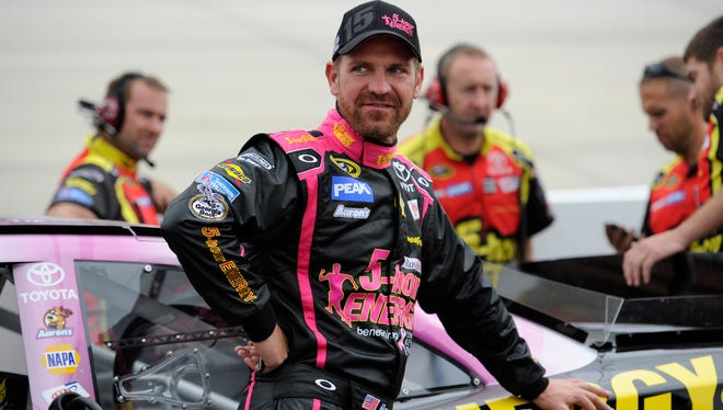 Clint Bowyer stands by his car on Friday before qualifying  for Sunday's Sprint Cup race. On Saturday, Bowyer tried his hand at yoga with NASCAR fans.