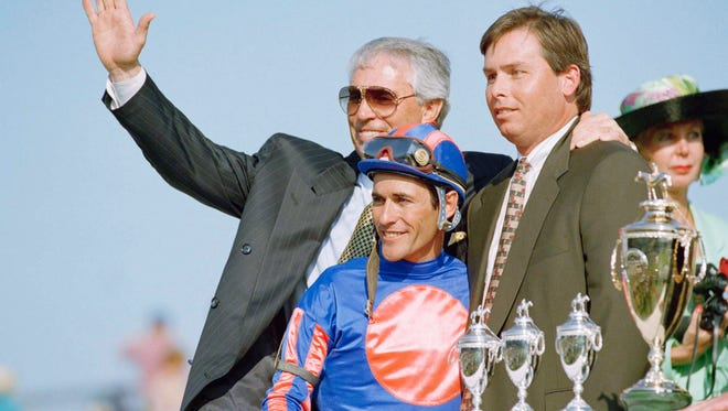 Trainer D. Wayne Lukas, left, jockey Gary Stevens, and assistant trainer Jeff Lukas, right, celebrate in the winners circle after Thunder Gulch won the 121st running of the Kentucky Derby, at Churchill Downs on Saturday, May 6, 1995, in Louisville, Ky. Jeff Lukas is the son of Wayne Lukas. (AP Photo/Ed Rainke)