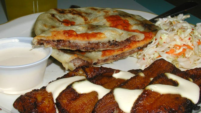 A traditional meal can include fried plantains with sweet cream topping, cabbage salad and a pupusa filled with melty cheese and bean. In the background is a glass of fruitas mixtas.