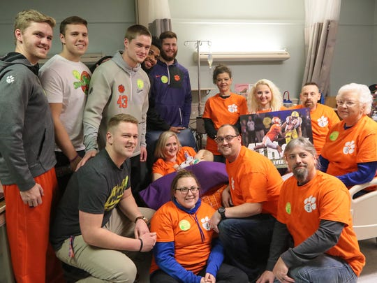 Clemson football players, from left, Austin Spence, Isaac Moorhouse, Daniel Funderburk, Sean Pollard, Chad Smith, and Christian Wilkins pose with the family of one-year old Hudson Belviso of Spartanburg, on Thursday at the Shriners Hospitals for Children in Greenville.