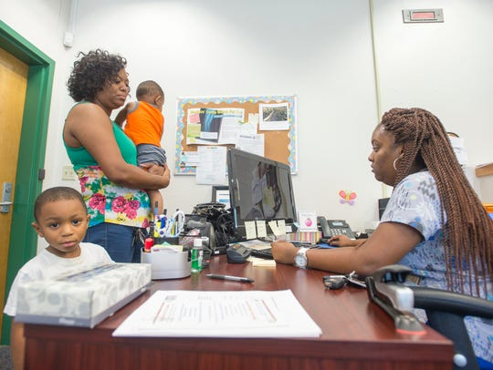 Matthew McCarty, 3, left, waits as medical assistant