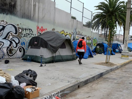 A pedestrian walks past a homeless encampment alongside a street in downtown Los Angles on May 31, 2017. The number of homeless people counted in Los Angeles County has jumped 23 percent, quadrupling the percentage increase from a year earlier.