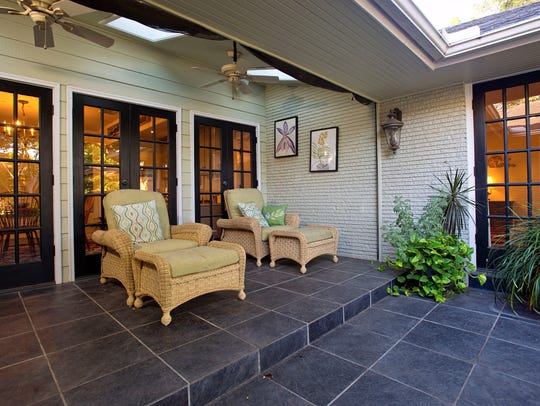 A sky light lit slate tiled patio is open to the living