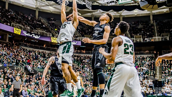 MSU's Marvin Clarklays the ball in despite the defensive pressure of Everson Davis of Binghamton in the first half Saturday in East Lansing.