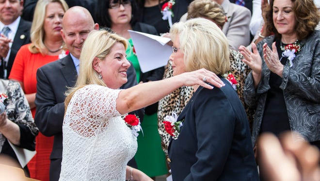 House Majority Leader Valerie J. Longhurst, D-Bear, (left) hugs equal pay figure Lilly Ledbetter at a bill signing ceremony on the steps of Legislative Hall in Dover on Thursday evening. Ledbetter's fight for equal pay for women led Congress to passing a 2009 law.