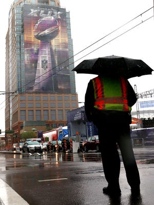 Phoenix Police officer Tim Bush directs traffic along Washington and First St. in the rain just two days before Super Bowl 49, Friday Jan. 30, 2015 in Phoenix.